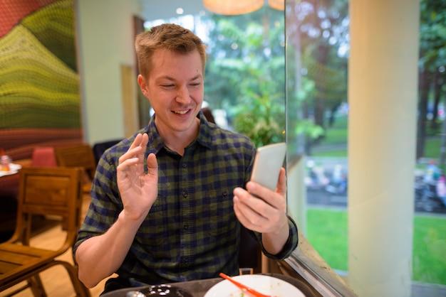 Homem jovem turista vlogging com telefone móvel no restaurante