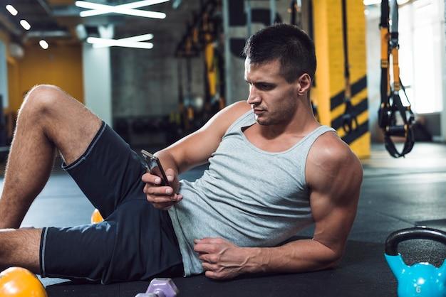 Homem jovem, usando, cellphone, em, ginásio