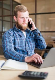 Homem jovem, usando, cellphone, enquanto, trabalhando, laptop, em, escritório