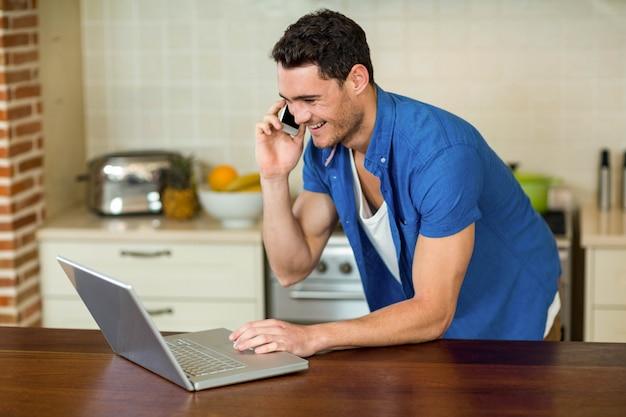 Homem jovem, usando computador portátil, e, conversa telefone, em, cozinha