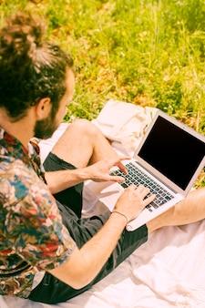 Homem jovem, usando computador portátil, ligado, natureza