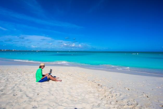 Homem jovem, usando computador portátil, ligado, praia tropical