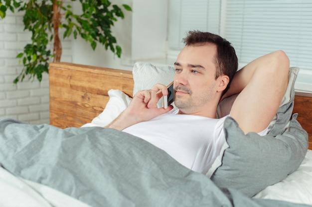 Homem jovem, usando, seu, telefone móvel, em, seu, quarto