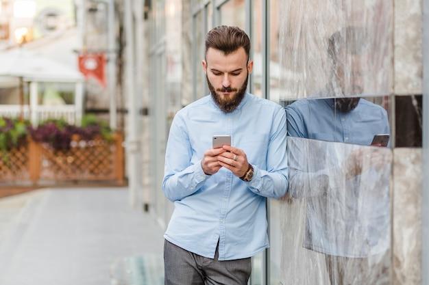 Homem jovem, usando, smartphone, em, ao ar livre