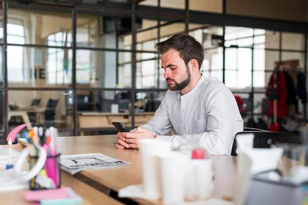Homem jovem, usando, smartphone, sentando, em, escritório