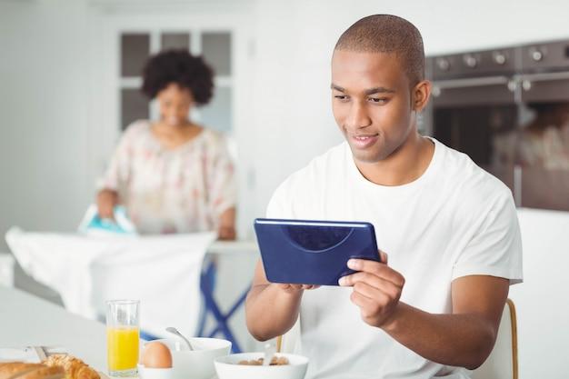 Homem jovem, usando, tabuleta, em, cozinha, e, dela, namorada, ironing