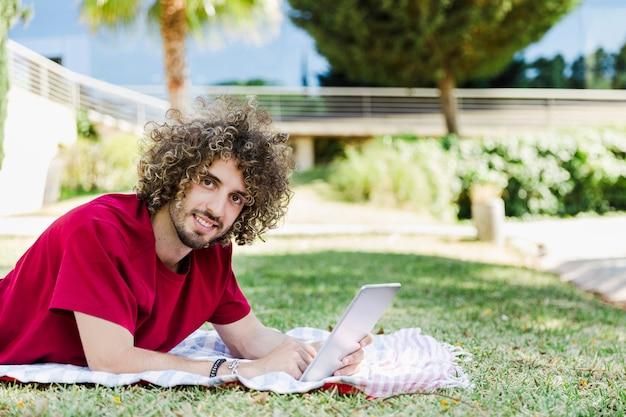 Homem jovem, usando, tabuleta, ligado, parque, chão