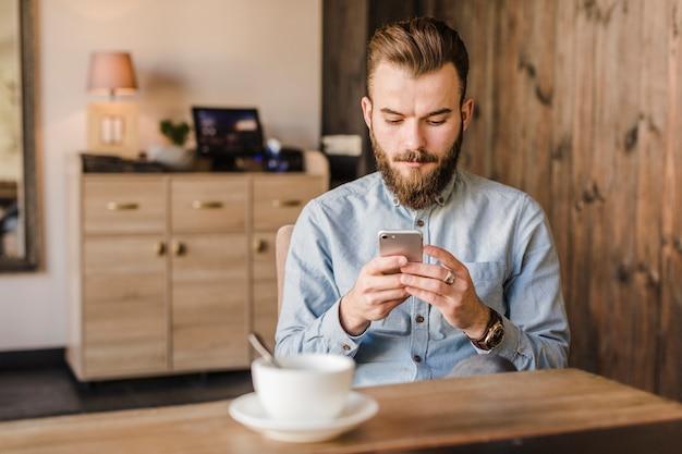 Homem jovem, usando, telefone móvel, com, xícara café, escrivaninha