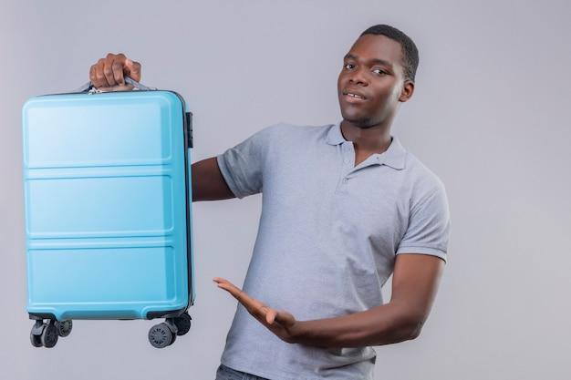 Homem jovem viajante afro-americano com camisa pólo cinza apresentando sua mala de viagem azul sorrindo confiante