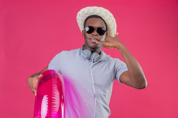 Homem jovem viajante afro-americano com chapéu de verão com fones de ouvido em volta do pescoço e óculos escuros segurando um anel inflável, sorrindo confiante fazendo gesto de me ligar sobre rosa