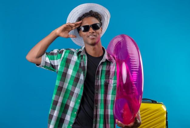 Homem jovem viajante afro-americano com chapéu de verão e óculos escuros em pé com uma mala segurando um anel inflável, saudando e sorrindo sobre o fundo azul
