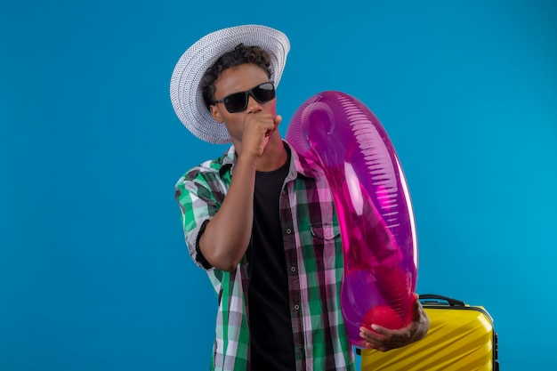 Homem jovem viajante afro-americano com chapéu de verão e óculos escuros em pé com uma mala segurando um anel inflável, tossindo sobre o fundo azul