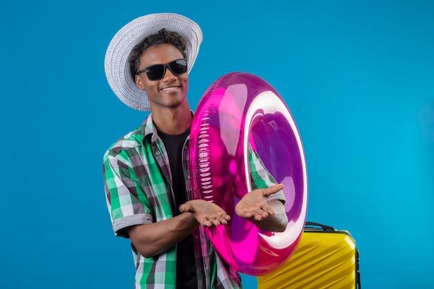 Homem jovem viajante afro-americano com chapéu de verão usando óculos escuros em pé com uma mala segurando um anel inflável segurando os braços juntos pedindo dinheiro, sorrindo sobre o fundo azul