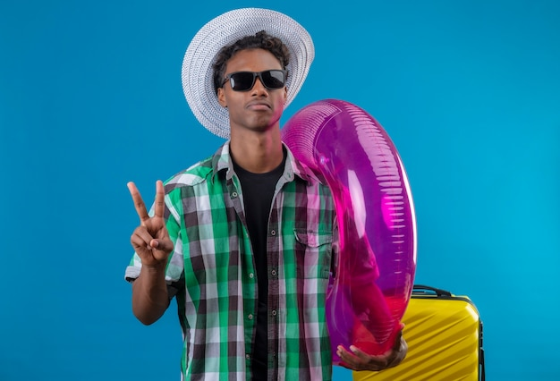 Homem jovem viajante afro-americano com chapéu de verão usando óculos escuros pretos em pé com uma mala segurando um anel inflável mostrando o número dois ou o sinal da vitória, olhando para a câmera com uma cara séria
