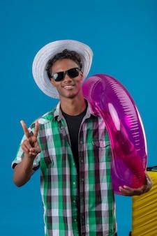 Homem jovem viajante afro-americano com chapéu de verão usando óculos escuros pretos em pé com uma mala segurando um anel inflável, mostrando o número dois ou o sinal da vitória, olhando para a câmera, sorrindo alegremente.