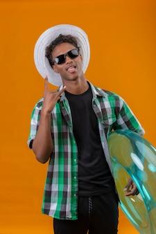 Homem jovem viajante afro-americano com chapéu de verão, usando óculos escuros pretos, segurando um anel inflável, fazendo um sinal de pedra, mostrando a língua, se divertindo, olhando para a câmera em pé sobre as costas laranja