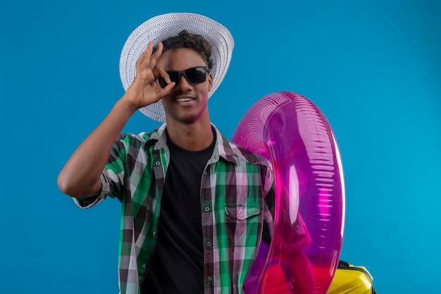 Homem jovem viajante afro-americano com chapéu de verão usando óculos escuros segurando um anel inflável e sorrindo alegremente fazendo o sinal de ok olhando para a câmera através desta placa sobre o verso azul