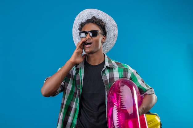 Homem jovem viajante afro-americano com chapéu de verão usando óculos escuros, segurando um anel inflável, olhando de lado, gritando ou chamando alguém em pé sobre um fundo azul