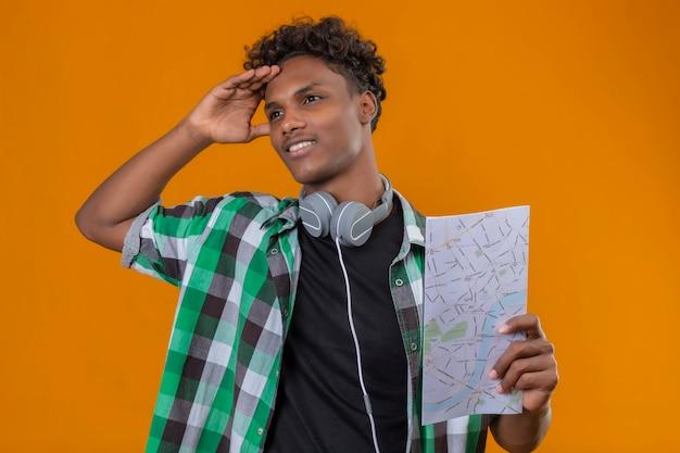 Homem jovem viajante afro-americano com fones de ouvido segurando um mapa, olhando de lado perplexo em pé sobre um fundo laranja