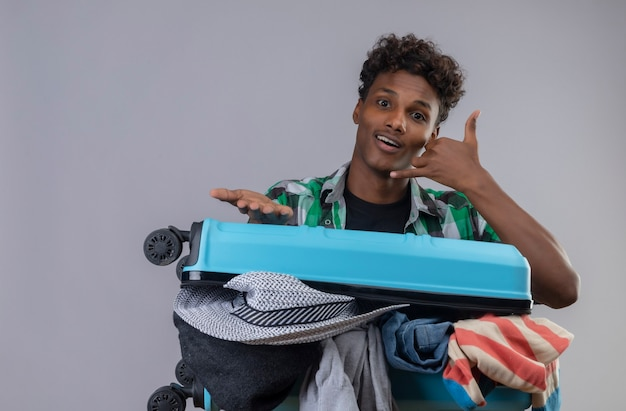 Homem jovem viajante afro-americano com mala cheia de roupas fazendo gesto de me chamar com a mão parecendo surpreso