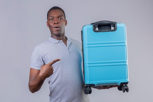 Homem jovem viajante afro-americano com uma camisa pólo cinza segurando uma mala azul apontando com o dedo para ela, parecendo surpreso e feliz