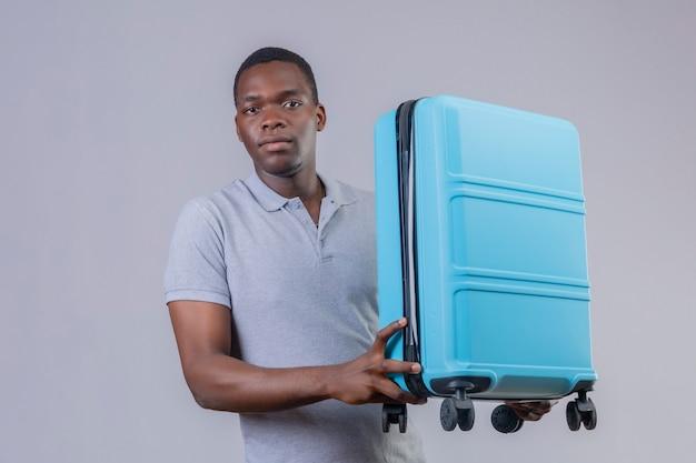 Homem jovem viajante afro-americano com uma camisa pólo cinza segurando uma mala azul com uma expressão séria e confiante no rosto