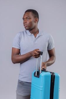 Homem jovem viajante afro-americano com uma camisa pólo cinza segurando uma mala azul e olhando para o lado muito ansioso