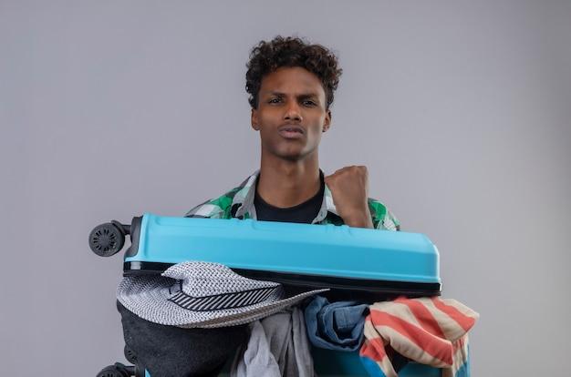 Homem jovem viajante afro-americano com uma mala cheia de roupas levantando o punho, parecendo confiante e regozijando-se com seu sucesso