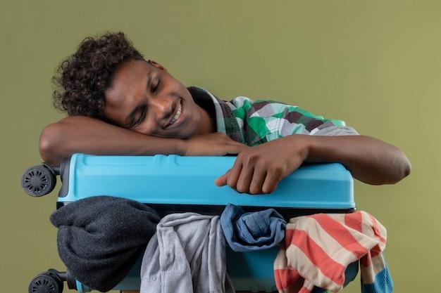 Homem jovem viajante afro-americano com uma mala cheia de roupas, parecendo cansado de dormir sobre ela sobre fundo verde.