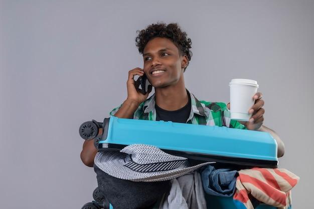 Homem jovem viajante afro-americano com uma mala cheia de roupas, segurando uma xícara de café enquanto fala no celular, sorrindo com uma cara feliz