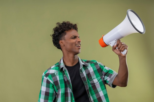 Homem jovem viajante afro-americano gritando para o megafone em pé sobre fundo verde