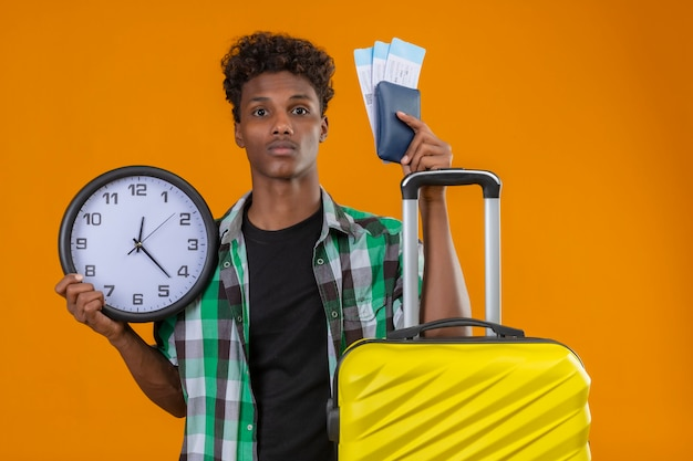 Homem jovem viajante afro-americano parado com uma mala segurando passagens aéreas e um relógio parecendo preocupado e confuso sobre um fundo laranja