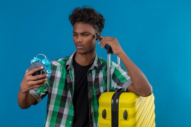 Homem jovem viajante afro-americano parado com uma mala segurando um despertador olhando para ele preocupado com o fundo azul