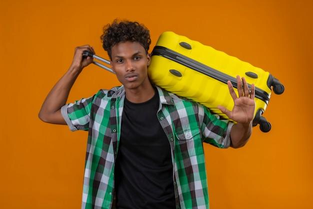 Homem jovem viajante afro-americano segurando mala com a mão aberta, fazendo sinal de pare, gesto de defesa sobre fundo laranja
