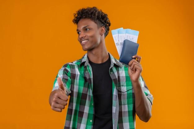 Homem jovem viajante afro-americano segurando passagens aéreas, sorrindo alegremente, positivo e feliz, olhando de lado mostrando os polegares em pé sobre um fundo laranja
