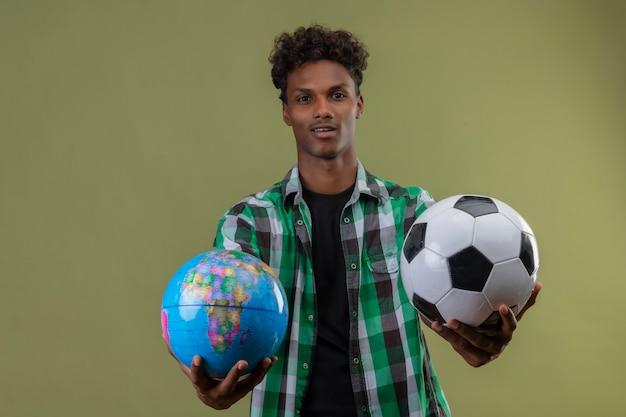 Homem jovem viajante afro-americano segurando um globo e uma bola de futebol, olhando para a câmera, sorrindo feliz e positivo em pé sobre o fundo verde
