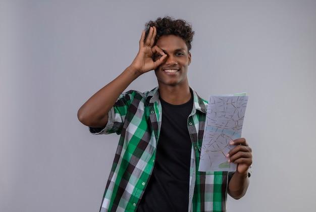 Homem jovem viajante afro-americano segurando um mapa, sorrindo, fazendo sinal de ok, olhando para a câmera através deste sinal em pé sobre um fundo branco