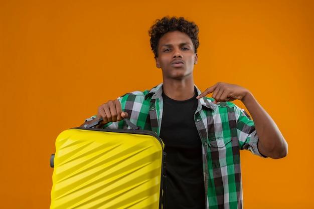 Homem jovem viajante afro-americano segurando uma mala apontando com o dedo para si mesmo, parecendo confiante e satisfeito sobre um fundo laranja