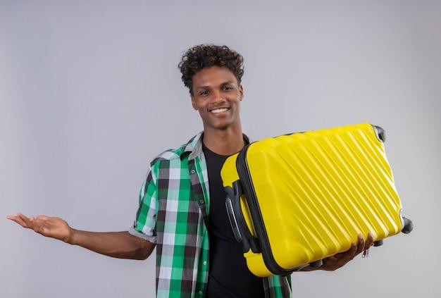 Homem jovem viajante afro-americano segurando uma mala e apresentando o espaço da cópia com o braço da mão sorrindo alegremente