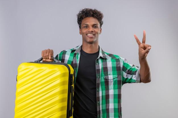 Homem jovem viajante afro-americano segurando uma mala, olhando para a câmera, sorrindo alegremente, positivo e feliz, mostrando o número dois ou o sinal da vitória em pé sobre um fundo branco