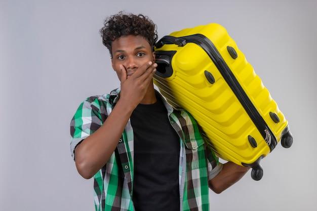 Homem jovem viajante afro-americano segurando uma mala surpreso e surpreso ao olhar para a câmera cobrindo a boca com a mão em pé sobre um fundo branco