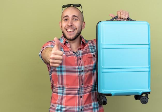 Homem jovem viajante alegre segurando a mala e dedilhando isolado na parede verde oliva com espaço de cópia