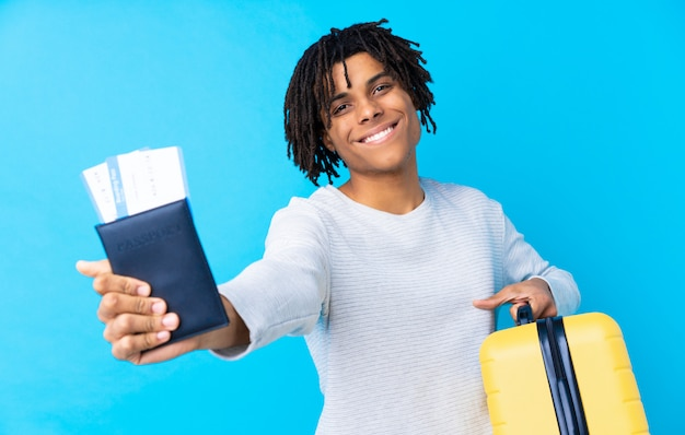 Homem jovem viajante americano africano, segurando uma mala e um passaporte