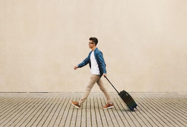 Homem jovem viajante andando com mala na rua. conceito de viagens.