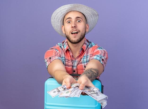 Homem jovem viajante animado com chapéu de praia de palha segurando dinheiro atrás de uma mala, isolado na parede roxa com espaço de cópia