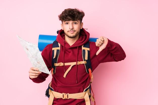 Homem jovem viajante árabe segurando um mapa mostrando um gesto de antipatia, polegares para baixo. conceito de desacordo.