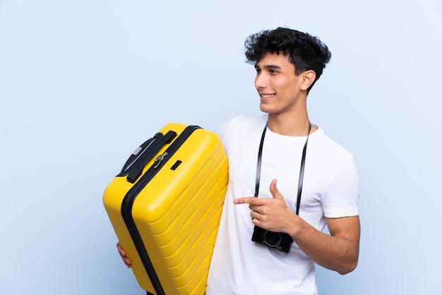 Homem jovem viajante argentino apontando para o lado para apresentar um produto