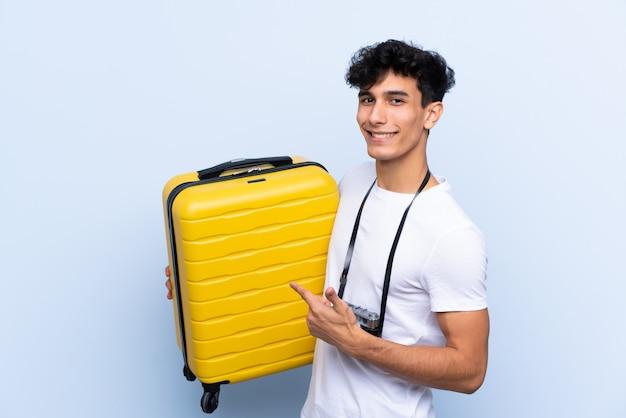 Homem jovem viajante argentino isolado parede azul e apontando-o