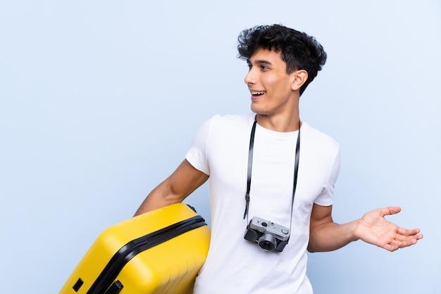 Homem jovem viajante argentino sobre parede azul isolada com expressão facial de surpresa