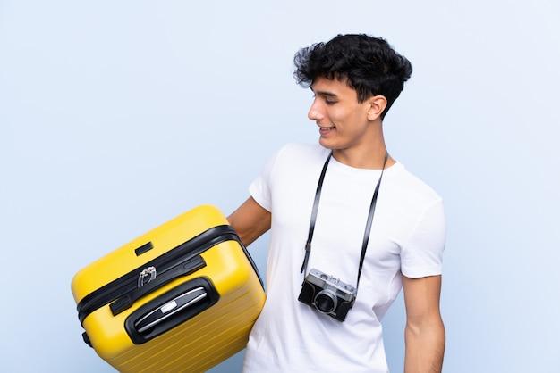 Homem jovem viajante argentino sobre parede azul isolada com expressão feliz